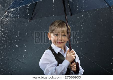 smiling boy dressed in white shirt and black vest standing under umbrella in rain