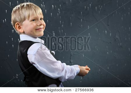 smiling boy dressed in white shirt and black vest stands in rain and catches drops by hands