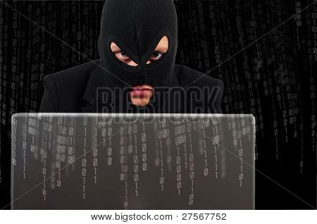 A Hacker With A Laptop Against Binary Background