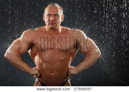 Thoughtful tanned undressed bodybuilder stands in rain.