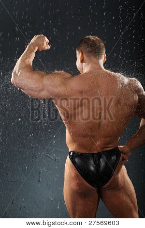 Undressed bodybuilder stands in rain back to camera and shows muscles of hand