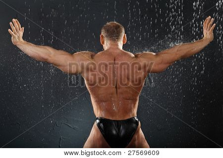 Undressed bodybuilder stands in rain back to camera and his arms in side
