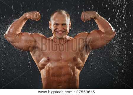 Smiling tanned undressed bodybuilder shows his muscles in rain.