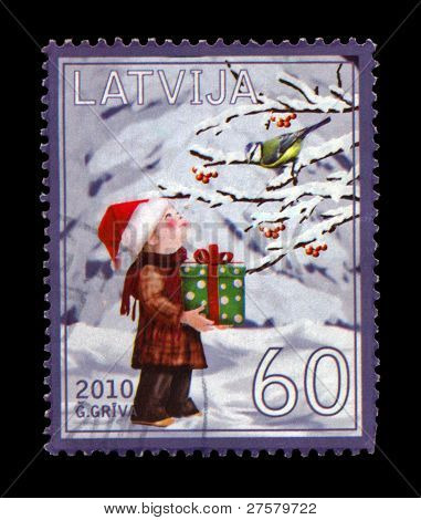 Latvia - Circa 2010: Cancelled Stamp Printed In Latvia, Shows Boy With Red Hat, Green Box With Prese