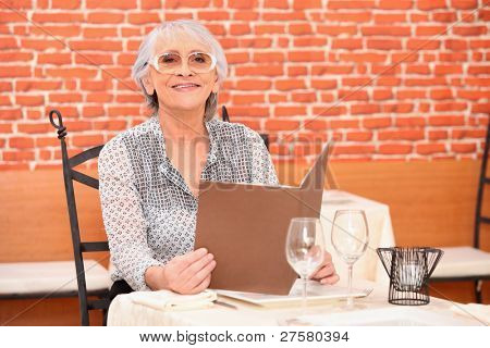 Older woman perusing a restaurant menu