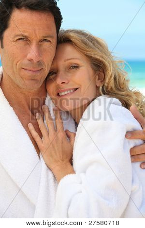Couple in toweling robes by the ocean