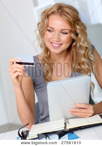 Beautiful woman doing online shopping in office