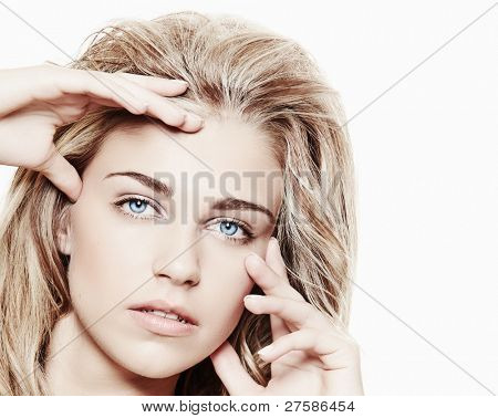 beautiful blond woman with long curly hair on white background touching her face