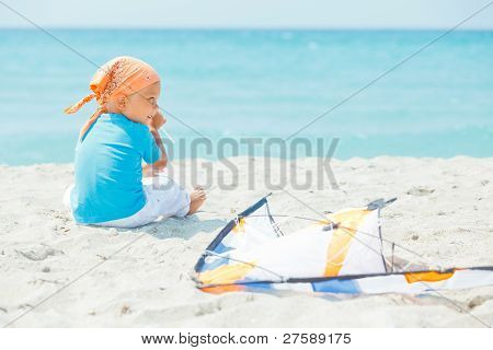 Cute boy on beach playing with a colorful kite