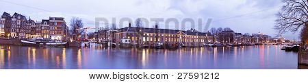 Panoramic city scenic with the Thiny Bridge at night in Amsterdam the Netherlands