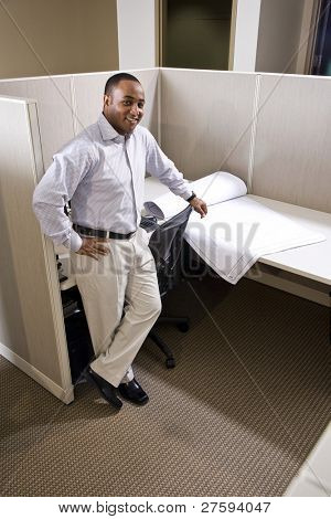 African American office worker standing in cubicle with floor plans