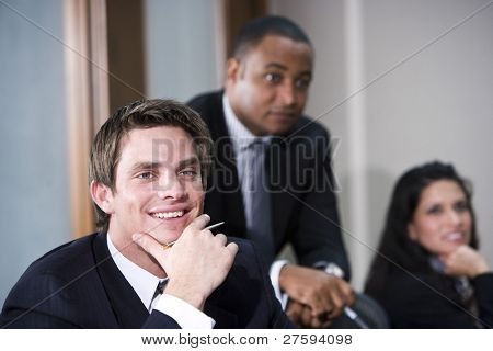 Confident young businessman with African American and Hispanic colleagues in background