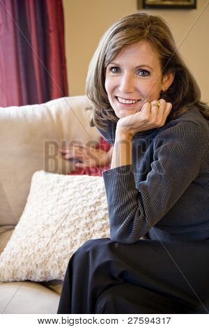 Attractive mature woman relaxing on couch in elegant modern living room
