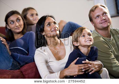 Familia interracial de cinco sentados juntos en el sofá mirando hacia arriba viendo la televisión
