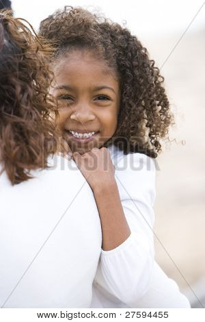 Close-up of cute six year old African-American girl in mother's arms