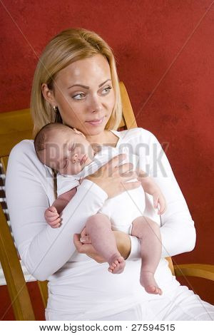 Happy young mother holding newborn baby boy in arms