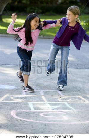 Multiracial friends having fun playing hopscotch on driveway