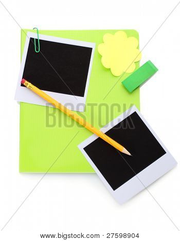 Photo papers and green notebook isolated on white