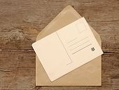 Blank vintage postcard and envelope on old wooden background