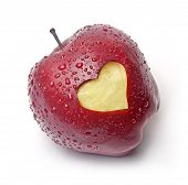 image of love bite  - Fresh red apple with a heart symbol against white background - JPG