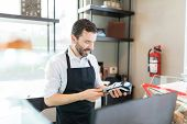Confident Baker Inserting Credit Card In Pos Terminal At Shop poster