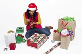 picture of upcoming  - Young lady preparing gifts for the upcoming Christmas holiday wearing Santa Claus hat - JPG