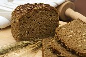 stock photo of whole-grain  - whole grain bread and slices with wheat and barley - JPG