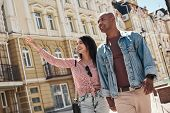 Romantic Relationship. Young Diverse Couple Walking On The City Street Holding Hands Sightseeing Smi poster