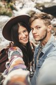 Happy Hipster Couple Making Selfie And Smiling At Waterfall In Forest Mountains. Stylish Couple In L poster