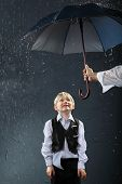 smiling boy dressed in white shirt and black vest standing under umbrella in rain; man hand holds um