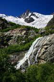 stock photo of firn  - Waterfalls and glaciers and green valleys. Exotic picture - ice water forest summer in one palette