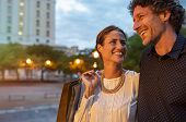Cheerful mature woman carring shopping bags in evening with her boyfriend. Loving couple enjoying va poster