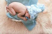 Adorable Newborn Baby Lying In Basket With Knitted Plaid On Fuzzy Rug, Top View poster
