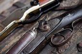 stock photo of hunt-shotgun  - Two old rifles sit on a table - JPG