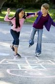 stock photo of hopscotch  - Multiracial friends having fun playing hopscotch on driveway - JPG
