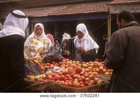 Veiled Arab Women Buy Apples In A Street Market