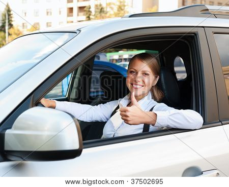 smiley woman sitting in car and showing thumbs up