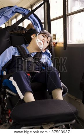 Disabled Little Boy Sitting In Wheelchair On School Bus