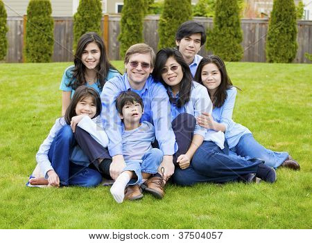 Large Family Of Seven Sitting Together On Lawn, Dressed In Blue Colors