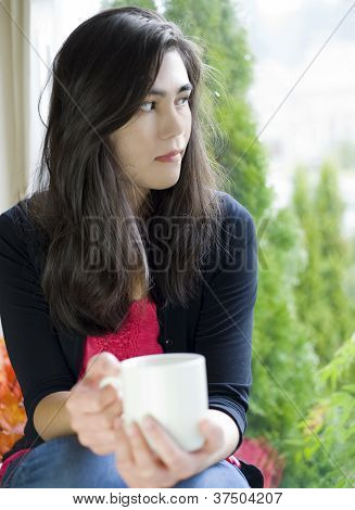 Beautiful Teenage Girl Holding Coffee Cup By Window, Sad Expression