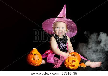 Halloween Baby Witch With A Carved Pumpkin Over Black Background