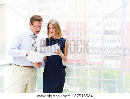 business man and business woman in the office to discuss reports