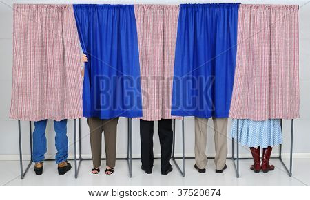 A row of five voting booths with men and women casting their ballots at a polling place. Horizontal format, only showing the legs of the voters, people are unrecognizable..