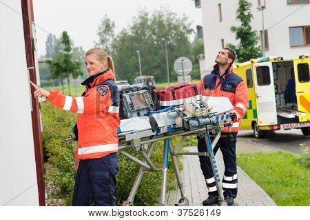 Paramedics with medical equipment ringing doorbell ambulance house call aid