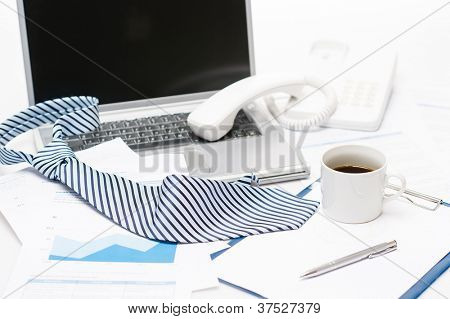 Man's tie laying on business office desk over laptop charts
