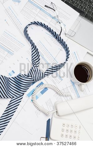 Busy office desk tie lying on paper charts business meeting