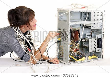 business woman tangled with cables trying to plug  wire on computer