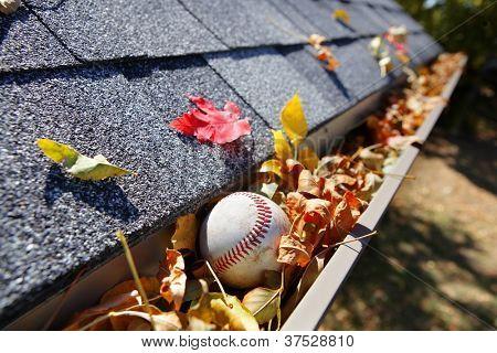 Calha de chuva cheio de Outono folhas com uma bola de beisebol