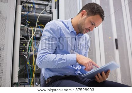 Man using tablet pc beside servers in data center