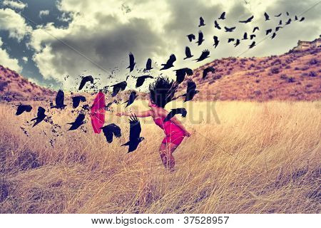 a girl in a field with an umbrella pointing toward a flock of birds